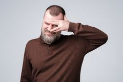 Man with beard in brown pulover peeping through fingers stock images