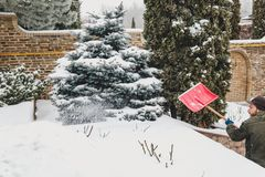 Snow removal in winter yard of private home. Man with a beard brushing the snow red plastic shovel in the yard of a private house. On the terrace, grow trees Stock Images
