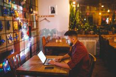 Man with beard businessman working behind laptop in coffee shop in evening. interior decorated with Christmas decor, light bulbs a. Re shining, hands on keyboard Royalty Free Stock Image