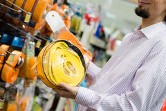 The man with beard buying yellow tow rope at the shopping store closeup on hand on the supermarket display shelf background. Closeup on hands of buying yellow Stock Image