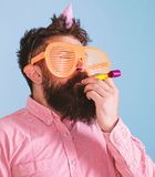 Man with beard on calm face holds party horn, light blue background. Guy in party hat with holiday attributes celebrates. Hipster in giant glasses blows into royalty free stock image