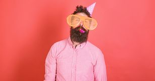 Man with beard on calm face with party horn, red background. Guy in party hat with holiday attributes celebrates. Surprise concept. Hipster in giant glasses royalty free stock photo