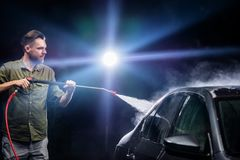 A man with a beard or car washer washes a gray car with a high-pressure apparatus at night in a car wash stock images