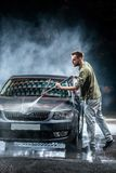 A man with a beard or car washer washes a gray car with a high - pressure washer at night in a shop wash stock image