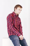 Man with beard in checkered red shirt sits on white cube Royalty Free Stock Photo