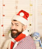 Man with beard in checkered shirt smiles widely. Guy in hat and scarf. Celebration and New Year decor concept. Santa Claus with cheerful face on wooden wall stock photos