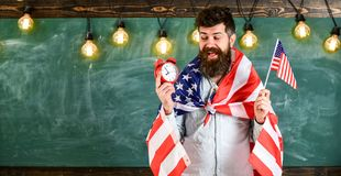 Man with beard on cheerful face holds flag of USA and clock, chalkboard on background, copy space. American educational. System concept. American teacher with Stock Images