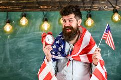 Man with beard on cheerful face holds flag of USA and clock, chalkboard on background, copy space. American teacher with. American flags holds alarm clock Stock Photography