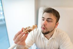 A man with a beard chewing a pizza. Student eats a tasty piece of pizza and looks at him attentively Royalty Free Stock Photo