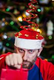 Man with beard in Christmas hat on background of tree royalty free stock image