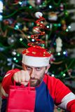 Man with beard in Christmas hat on background of tree royalty free stock photography