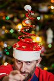 Man with beard in Christmas hat on background of tree royalty free stock photos