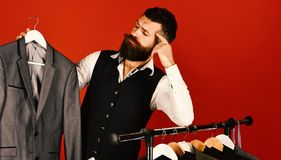 Man with beard by clothes rack. Designer looks at work. Man with beard in vest by clothes rack. Designer looks at his work near clothes hangers. Tailor with stock photo