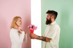 Man with beard congratulates woman birthday anniversary holiday. Hipster bearded give bouquet flowers to girlfriend royalty free stock images