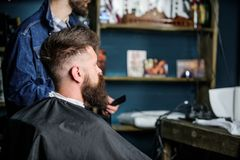Man with beard covered with black cape sits in hairdressers chair, beauty supplies background. Man with beard client of royalty free stock photography