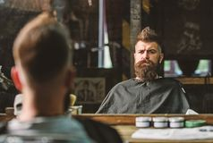 Man with beard covered with black cape sits in hairdressers chair in front of mirror. Hipster with beard checking result. Of haircut. Barbershop concept. Man royalty free stock images