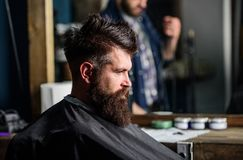 Man with beard covered with black cape sits in hairdressers chair, mirror background. Hipster with beard waits for stock image
