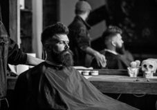 Man with beard covered with black cape sits in hairdressers chair, mirror background. Man with beard client of hipster stock photo