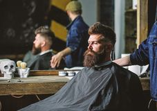 Man with beard covered with black cape sits in hairdressers chair, mirror background. Man with beard client of hipster stock photos