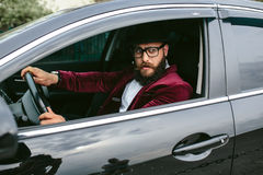 Man with beard driving a car Royalty Free Stock Photos