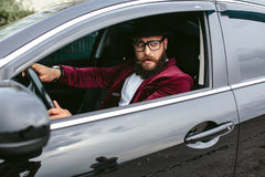 Man with beard driving a car Stock Images