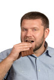 Man with beard eating chocolate Royalty Free Stock Image