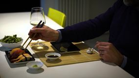 Man with a beard eating sushi and drinking white wine during the dinner stock footage