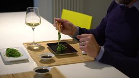 Man with a beard eating sushi and drinking white wine during the dinner stock video footage