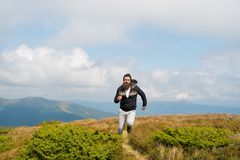 Man with beard enjoy freedom, runs on top of mountain. Hipster feels free while hiking, sky background. Hipster or. Brutal macho conquers mountain. Man with Royalty Free Stock Photo