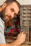 A man with a beard fixing the system unit Royalty Free Stock Images
