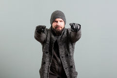 Man with beard gesturing with forefingers wearing cap and gloves Royalty Free Stock Photos
