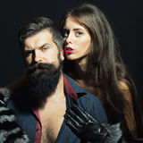 Man with beard and girl in gloves. Beautiful stylish young sensual couple of women in fur sleeves and gloves embraces men with long lush beard in shirt with bare Royalty Free Stock Photo