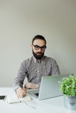 Man with beard in glasses taking notes with laptop and notepad Royalty Free Stock Images