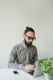 Man with beard in glasses typing laptop with smartphone Stock Photography