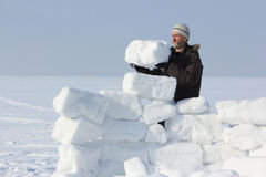 The man with a beard in a gray cap building an igloo. Of snow blocks  on a glade in the winter Stock Images