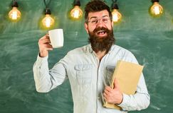 Man with beard on happy face in classroom.Teacher in eyeglasses holds book and mug of coffee or tea. Coffee break. Concept. Scientist holds book and mug of stock image