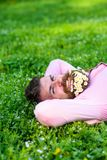 Man with beard on happy face enjoy nature. Unite with nature concept. Bearded man with daisy flowers in beard lay on. Meadow, grass background. Hipster with royalty free stock image
