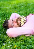 Man with beard on happy face enjoy nature. Unite with nature concept. Hipster with bouquet of daisies in beard relaxing. Bearded man with daisy flowers in stock image