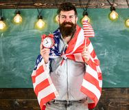 Man with beard on happy face holds flag of USA and clock in classroom, chalkboard on background. American educational. System concept. American teacher with Royalty Free Stock Photos