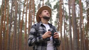Man with a beard and a hat with binoculars walking in the woods. Composition hiking, forester.