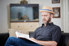 Man with beard and hat reads a book at home. In an old building Royalty Free Stock Image