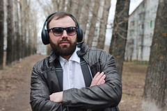 Man with beard and headphones in the park Royalty Free Stock Photo