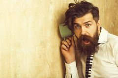 Man with beard hear gossip with cup. Guy listen at wall. Beauty and fashion. hipster with long hair. neighbour and secret, copy space royalty free stock photo