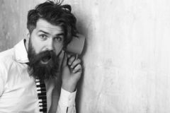 Man with beard hear gossip with cup. Guy listen at wall. Beauty and fashion. hipster with long hair. neighbour and secret, copy space royalty free stock image