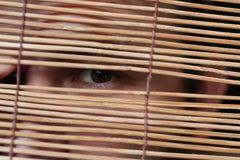 Eyes looking through the blinds. A man with a beard hides behind a wooden Roman Blinds and expresses his emotions Stock Image