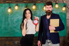 Man with beard hold book and sexy girl teacher holds alarm clock, chalkboard on background. Lady teacher and strict. Schoolmaster care about discipline and Stock Image