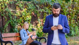 Man with beard hold smartphone while girl sit bench park. Man use application for dating. Guy looking for girlfriend. Dating application concept. Application stock images