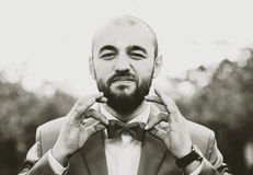 Man with beard holding his bow tie by fingers, grain effect Royalty Free Stock Image