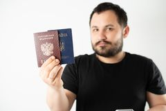 A man with a beard holding a passport of Russia and Ukraine translation: - Ukraine. Passport, Russian Federation. A man with a beard on a light background royalty free stock photo