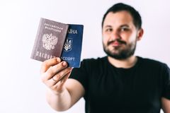 A man with a beard holding a passport of Russia and Ukraine translation: - Ukraine. Passport, Russian Federation. A man with a beard on a light background royalty free stock image